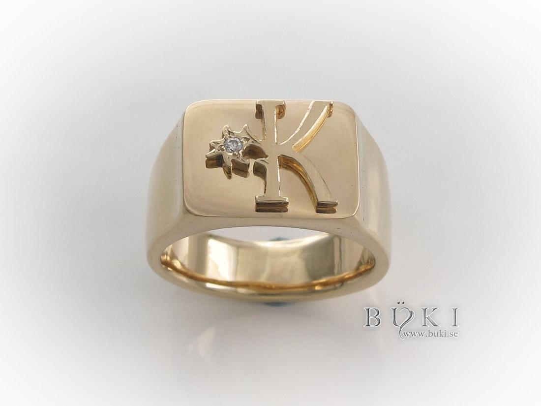 klackring-i-18k-guld-med-logga-och-diamant