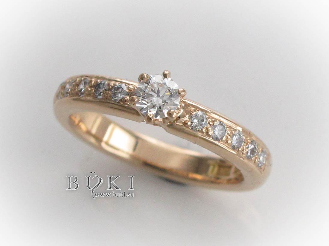 alliansring-i-18k-guld-med-fadeninfattade-sidostenar-och-stor-diamant-i-låg-6-klo-infattning